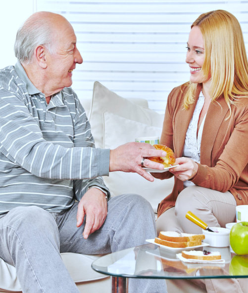 caregiver and senior couple having conversation