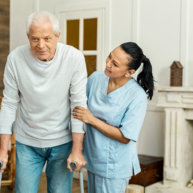 caregiver helping the senior man to walk