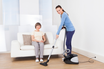 caretaker cleaning floor with vacuum cleaner while senior woman sitting on sofa