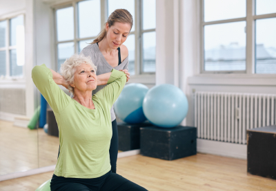 senior woman doing light pilates workout with her personal assistant